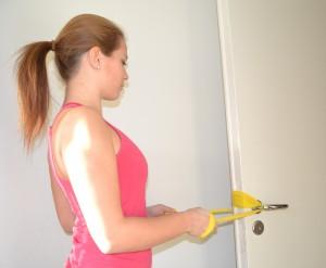 Rodd med gummiband fäst runt dörrhandtag. Dra armbågarna bakåt och tänk på att dra ihop skulderbladen och hålla axlarna nere.