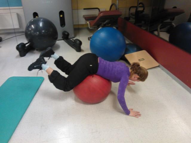 Utgångsläge. Ligg på en pilatesboll med mage och höften på bollen.