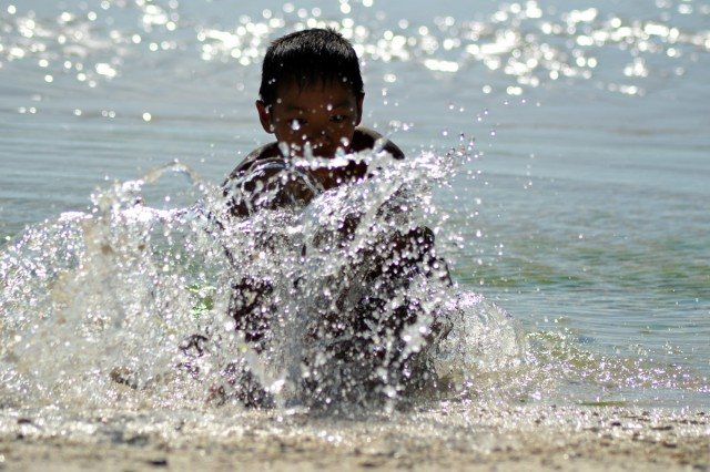 En filippinsk pojke som fångar småfisk på sitt eget sätt med bara händerna